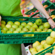 Female Worker Holding Crate Full Of Apples In Grocery Store — Stock Photo