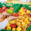 Shopper purchasing apples in supermarket — Stock Photo #26947479