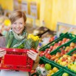 Woman Carrying Shopping Basket In Grocery Store — Stock Photo