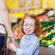 Girl Sticking Out Tongue While Holding Mothers Hand In Grocery — Stock Photo #26947493