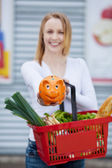 Woman holding piggy bank and shopping basket — Stock Photo