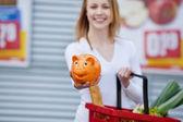 Woman Showing Piggybank While Holding Shopping Basket — Stock Photo