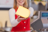 Saleswoman showing cheese chunk — Stock Photo
