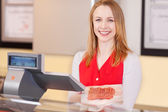 Friendly female worker at the cash counter — Stock Photo