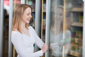 Smiling blond woman buying frozen food — Stock Photo