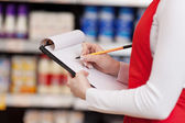 Saleswoman Writing On Clipboard In Grocery Store — Stockfoto