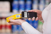 Woman's Hands Scanning Barcode With Mobile Phone In Supermarket — Stock Photo