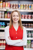 Saleswoman With Arms Crossed Standing In Grocery Store — Stock Photo