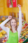 Female Worker With Arms Raised In Grocery Store — Stock Photo