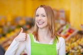 работница, показывая thumbsup жест в продуктовый магазин — Стоковое фото