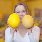 Woman holding two different melons — Stock Photo