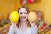 Female with a sweet smile showing melons — Stock Photo