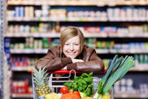 Woman with a shopping cart of fresh produce — Stock Photo