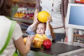 Girl Giving Muskmelon To Cashier For Billing At Supermarket — Stock Photo
