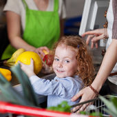 Cute girl buying a melon in the supermarket — Stock Photo