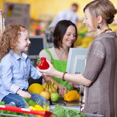 Woman Giving Capsicum To Daughter At Cash Counter In Supermarket — Stock Photo