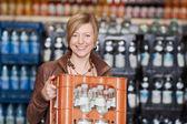 женщина, перевозящих обрешеткой бутылки воды в супермаркете — Стоковое фото