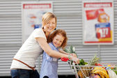 Girl And Mother Pushing Shopping Cart Together Outdoors — Stock Photo
