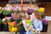 Smiling mother and daughter buying tulips — Stock Photo