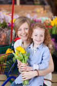 Girl And Mother Holding Flowers In Supermarket — Stock Photo
