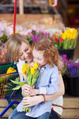 Mother and daughter buying tulips — Stock Photo