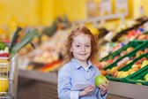 Beautiful little redhead girl with an apple — Stock Photo