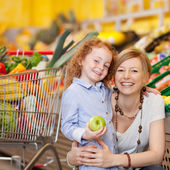 Girl Holding Apple While Mother Embracing Her In Grocery Store — Stock Photo