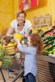 Dívka drží meloun cukrový v nákupní košík, zatímco matka při pohledu na — Stock fotografie