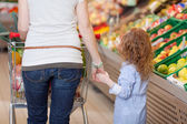 Mother holding her kids hand in supermarket — Stock Photo