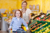 Pretty little girl and her mother in a supermarket — Stock Photo