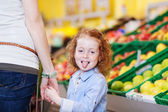 Girl Sticking Out Tongue While Holding Mothers Hand In Grocery — Stock Photo