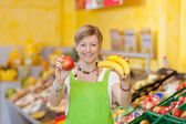 Friendly saleswoman showing different fruits — Stock Photo