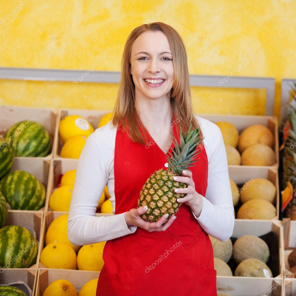 female worker holding pineapple in grocery store stock photo female worker holding pineapple in grocery store stock photo 26944289