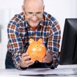 Mature man smiling at a piggy-bank at the office — Stock Photo