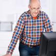 Man behind an office desk looking at the computer — Stock Photo
