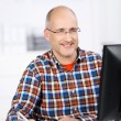 Mature man smiling when working at the office — Stock Photo #26975239