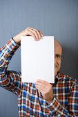 Balding man holding a blank paper in front of face — Stock Photo
