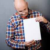 Balding man holding and looking at a blank paper — Stock Photo