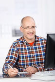 Mature man smiling when working at the office — Stock Photo