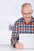 Mature man smiling when looking at the laptop — Stock Photo