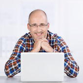 Friendly mature man smiling with a laptop — Stock Photo
