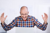 Joyful mature man looking at a laptop screen — Stock Photo