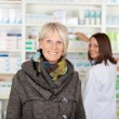 Foto de Stock  : Senior with scarf in pharmacy
