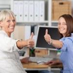 Businesswomen Gesturing Thumbs Up At Desk — Stock Photo