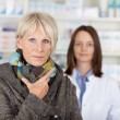 Stock Photo: Unwell Senior WomIn Sweater With Pharmacist In Background