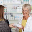 Female Pharmacist Giving Prescribed Medicine To Customer In Phar — Stock Photo #26988413