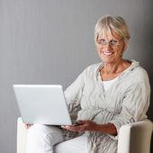 Donna senior con portatile seduti sul divano contro muro grigio — Foto Stock