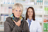 Unwell Senior Woman In Sweater With Pharmacist In Background — Stock Photo