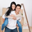 Man Giving Piggyback Ride To Woman Against Cardboard Boxes — Stock Photo #27009191