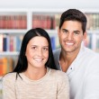 Happy couple standing in front of the bookshelf — Stock Photo
